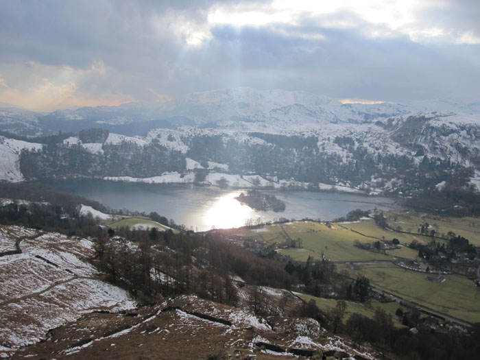 Rays of light beam down through the clouds on the lake of Grasmere