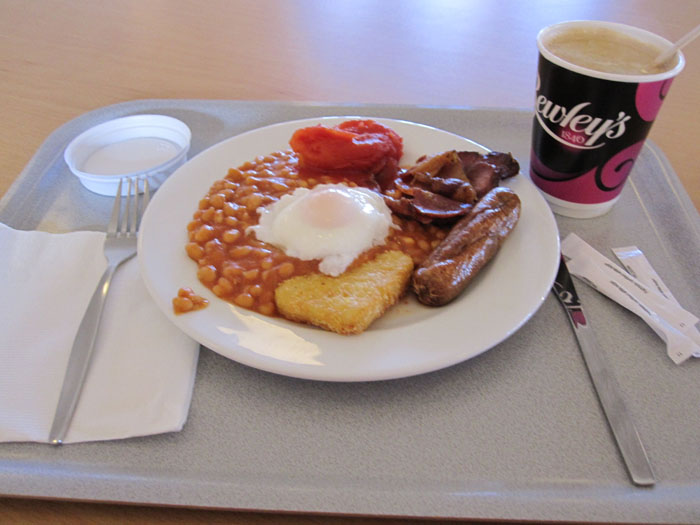 A Full English Breakfast: baked beans, poached egg, hash brown,  tomato, sausage, bacon, and tea