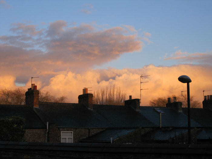 Clouds simply tumble away over the chimneys of the houses behind the Grange at sunset