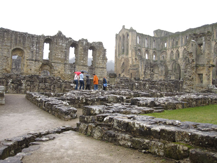 Exploring the ruins of the abbey and monastery at Rievaulx under our umbrellas
