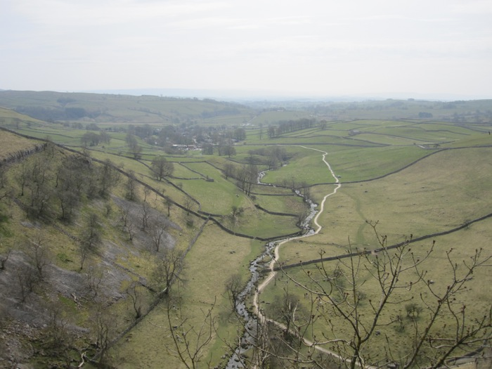 The rivulet winding and fading into the distance below