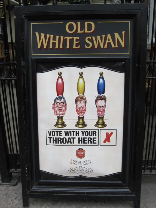 "Clever ""Vote with Your Throat"" advertisement outside the Old White Swan, York, complete with caricatures of Gordon Brown, Nick Clegg, and David Cameron"
